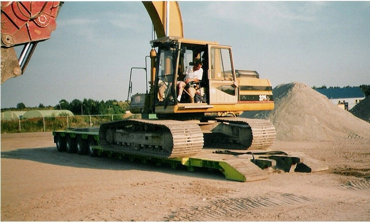 Cat 325 L met crusher wordt geladen.