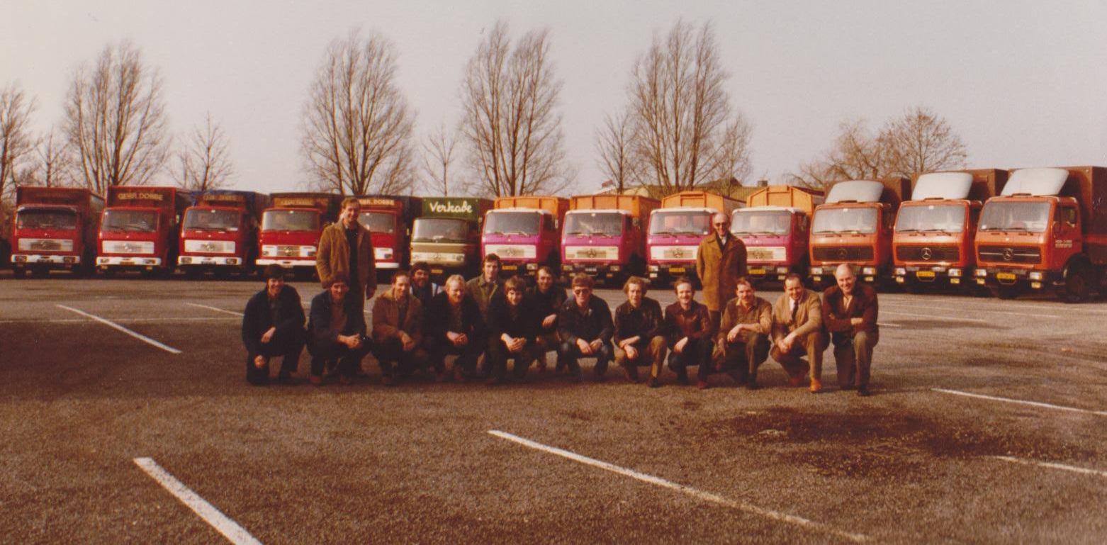 Alle-medewerkers-van-Gebr-Dobbe-in-1982-op-het-veilingterrein-bij-de-Korte-Goog--de-bomen-op-de-achtergrond-zijn-van-de-Sotaweg--De-drie-autos-rechts-op-de-foto-werden-ingezet-voor-Albert-Heijn-Bloemencentrale-daar