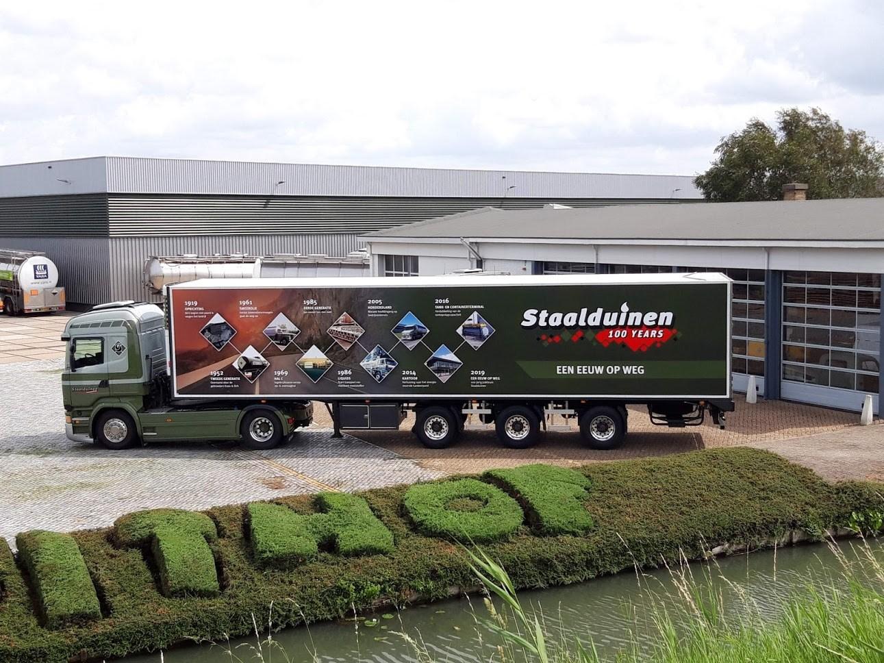 Staalduinen-Logistics-Maasdijk-bestaat-100-jaar--Deze-oplegger-is-nu-beplakt-met-de-verschillende-perioden-van-vervoer