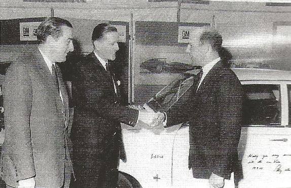 1967--Formule--coureur-Stirling-Moss-feliciteert-Michel-en-Ad-de-Groot-tijdens-de-ointroductie-van-de-nieuwe-Vauxhall-Viva