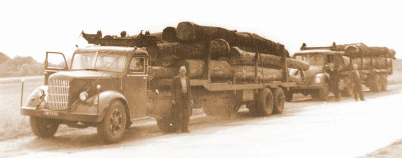Mack--en-Magirus-Deutz--Twee-zwaar-met-boomstammen-beladen-vrachtautos-van-Jan-Termaat-uit-Lexmond--Jo-van-Dijk-uit-Hei‐-en-Boeicop-was-chauffeur-bij-hem--Hij-staat-naast-de-vrachtwagen-
